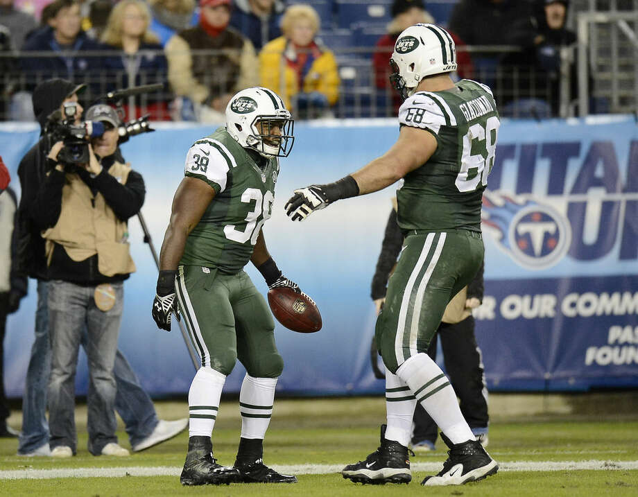 New York Jets fullback John Conner (38) celebrates with tackle Breno Giacomini (68) after Conner scored a touchdown against the Tennessee Titans on a 9-yard pass in the second half of an NFL football game Sunday, Dec. 14, 2014, in Nashville, Tenn. (AP Photo/Mark Zaleski)