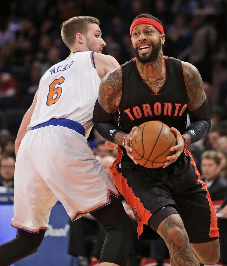 Toronto Raptors' James Johnson, right, pushes past New York Knicks' Travis Wear during the first half of an NBA basketball game, Sunday, Dec. 14, 2014 in New York. (AP Photo/Seth Wenig)