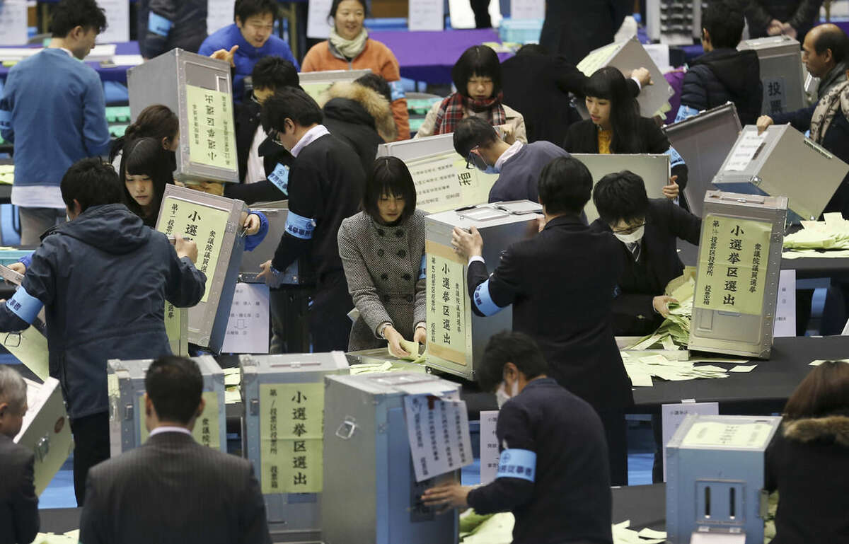 Election staff members open ballot boxes for vote counting in the parliamentary lower house elections at a ballot counting center in Tokyo, Sunday, Dec. 14, 2014. Japanese Prime Minister Shinzo Abe's ruling party was headed for a landslide victory in lower house elections Sunday, according to projections released soon after polls closed.(AP Photo/Koji Sasahara)