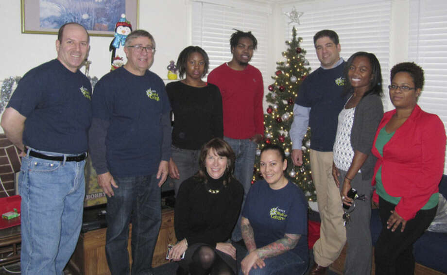 Contributed photoTauck employees, as well as staff and clients of Keystone House, with a Christmas tree donated by Tauck.