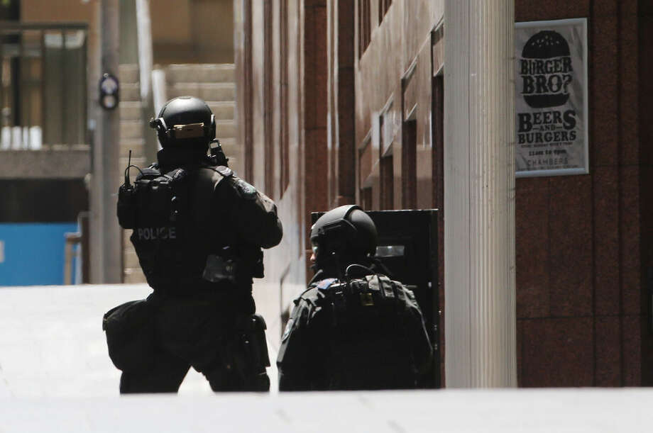Police stand at the ready close to a cafe under siege in Martin Place in the central business district of Sydney, Australia, Monday, Dec. 15, 2014. New South Wales state police would not say what was happening inside the cafe or whether hostages were being held. But television footage shot through the cafe's windows showed several people with their arms in the air. (AP Photo/Rob Griffith)
