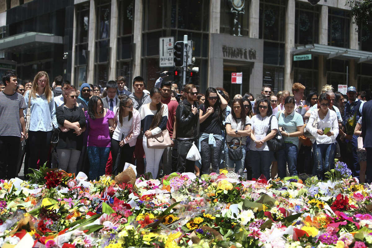 Staff members from the Lindt Chocolat Cafe with their arms linked pay tribute to their colleague who lost his live during a siege at the popular coffee shop at Martin Place in the central business district of Sydney, Australia, Tuesday, Dec. 16, 2014. The siege ended early Tuesday with a barrage of gunfire that left two hostages and the Iranian-born gunman dead, and a nation that has long prided itself on its peace rocked to its core. (AP Photo/Steve Christo)