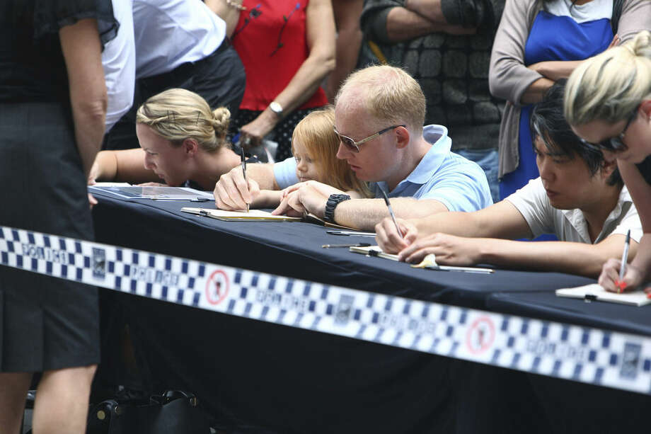 People sign tributes at a makeshift memorial after shootings during a siege at the Lindt Chocolat Cafe at Martin Place in the central business district of Sydney Australia. Tuesday, Dec. 16, 2014. Tearful Australians laid mounds of flowers at the site where a gunman held hostages for 16 hours at a popular Sydney cafe. The siege ended early Tuesday with a barrage of gunfire that left two hostages and the Iranian-born gunman dead, and a nation that has long prided itself on its peace rocked to its core. (AP Photo/Steve Christo)