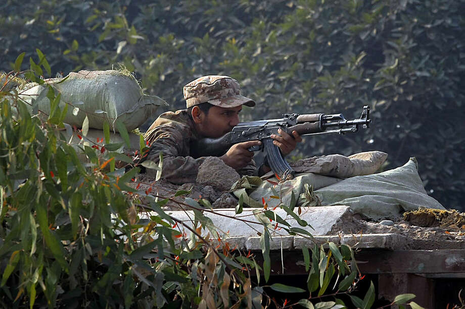 A Pakistani army soldier takes position on a bunker close to a school under attack by Taliban gunmen in Peshawar, Pakistan, Tuesday, Dec. 16, 2014. Taliban gunmen stormed a military school in the northwestern Pakistani city, killing and wounding dozens, officials said, in the latest militant violence to hit the already troubled region. (AP Photo/Mohammad Sajjad)