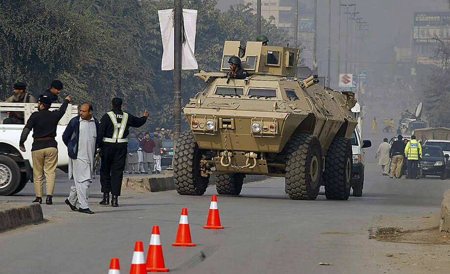 An armored personnel carrier moves toward a school under attack by Taliban gunmen in Peshawar, Pakistan,Tuesday, Dec. 16, 2014. Taliban gunmen stormed a military school in the northwestern Pakistani city, killing and wounding dozens, officials said, in the latest militant violence to hit the already troubled region. (AP Photo/Mohammad Sajjad)