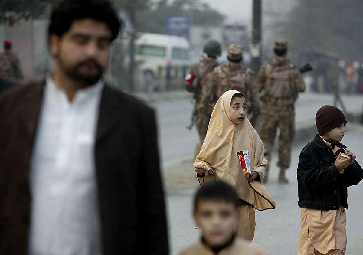 A family member escorts children outside a school attacked by the Taliban in Peshawar, Pakistan, Tuesday, Dec. 16, 2014. Taliban gunmen stormed a military-run school in the northwestern Pakistani city of Peshawar on Tuesday, killing and wounding scores, officials said, in the highest-profile militant attack to hit the troubled region in months. (AP Photo/B.K. Bangash)