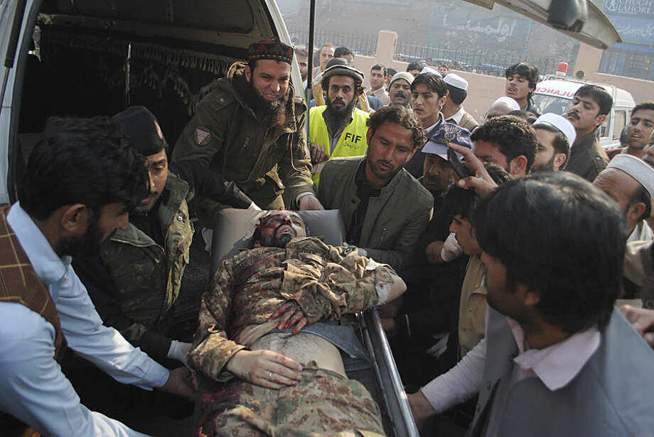The lifeless body of a Pakistani army officer, a victim of a Taliban attack in a school, is brought to a local hospital in Peshawar, Pakistan, Tuesday, Dec. 16, 2014. Taliban gunmen stormed a military-run school in the northwestern Pakistani city of Peshawar on Tuesday, killing and wounding scores, officials said, in the highest-profile militant attack to hit the troubled region in months.(AP Photo/Mohammad Sajjad)