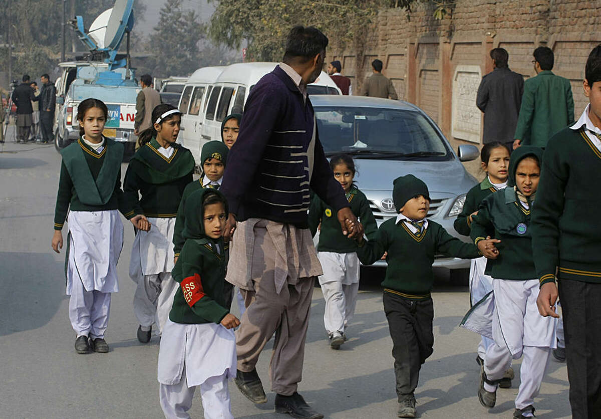 A plainclothes security officer escorts students rescued from nearby school during a Taliban attack in Peshawar, Pakistan, Tuesday, Dec. 16, 2014. Taliban gunmen stormed a military-run school in the northwestern Pakistani city, killing and wounding scores, officials said, in the worst attack to hit the country in over a year.(AP Photo/Mohammad Sajjad)