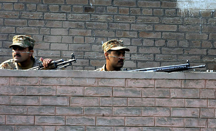 Pakistani army troops are positioned close to a school under attacked by Taliban gunmen in Peshawar, Pakistan, Tuesday, Dec. 16, 2014. Taliban gunmen stormed a military school in the northwestern Pakistani city, killing and wounding dozens, officials said, in the latest militant violence to hit the already troubled region. (AP Photo/Mohammad Sajjad)