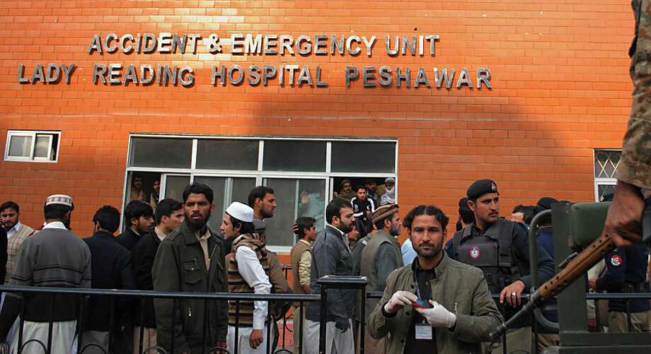People gather at a hospital, where victims of a Taliban attack are being treated in Peshawar, Pakistan, Tuesday, Dec. 16, 2014. Taliban gunmen stormed a military-run school in the northwestern Pakistani city of Peshawar on Tuesday, killing and wounding scores, officials said, in the highest-profile militant attack to hit the troubled region in months.(AP Photo/Mohammad Sajjad)