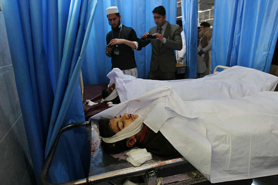 Pakistanis use their mobile phones to take photographs of students who died in a Taliban attack on their school, at a local hospital in Peshawar, Pakistan, Tuesday, Dec. 16, 2014. Taliban gunmen stormed a military-run school in the northwestern Pakistani city, killing and wounding scores, officials said, in the worst attack to hit the country in over a year.(AP Photo/Mohammad Sajjad)