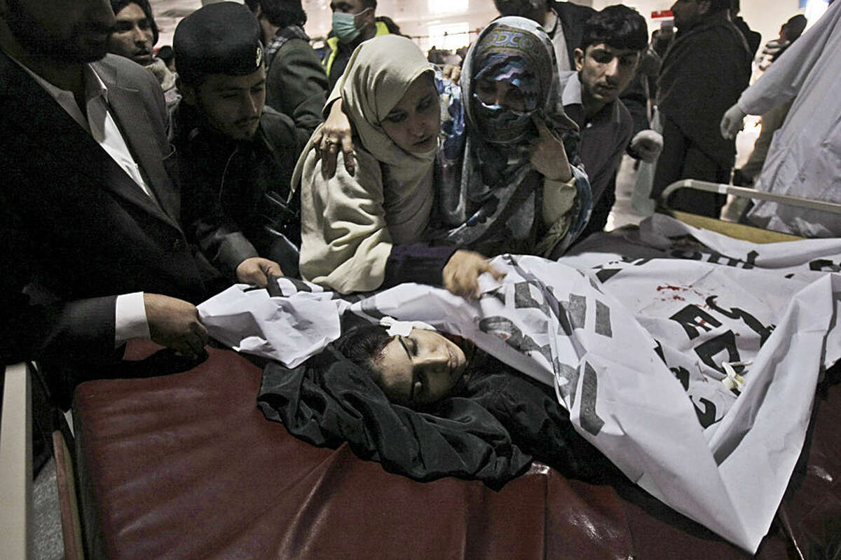 Relatives of a victim of a Taliban attack in a school, mourn over her lifeless body at a hospital in Peshawar, Pakistan, Tuesday, Dec. 16, 2014. Taliban gunmen stormed a military-run school in the northwestern Pakistani city of Peshawar on Tuesday, killing and wounding scores, officials said, in the highest-profile militant attack to hit the troubled region in months.(AP Photo/Mohammad Sajjad)