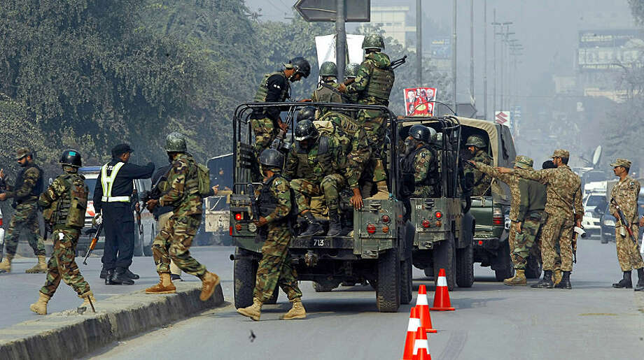 Pakistani army troops arrive to conduct an operation at a school under attack by Taliban gunmen in Peshawar, Pakistan, Tuesday, Dec. 16, 2014. Taliban gunmen stormed a military school in the northwestern Pakistani city, killing and wounding dozens, officials said, in the latest militant violence to hit the already troubled region. (AP Photo/Mohammad Sajjad)