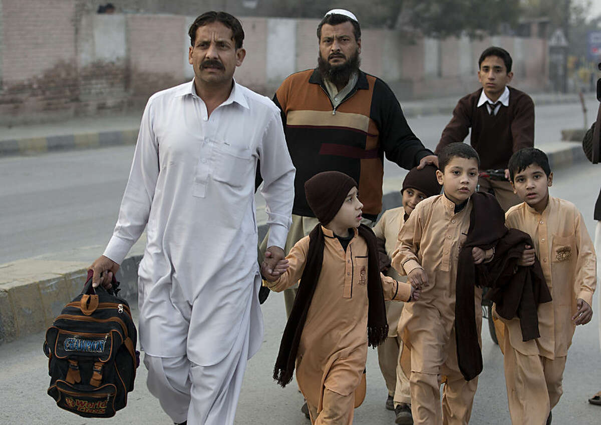 Pakistani parents escort their children outside a school attacked by the Taliban in Peshawar, Pakistan, Tuesday, Tuesday, Dec. 16, 2014. Taliban gunmen stormed a military-run school in the northwestern Pakistani city of Peshawar on Tuesday, killing and wounding scores, officials said, in the highest-profile militant attack to hit the troubled region in months. (AP Photo/B.K. Bangash)