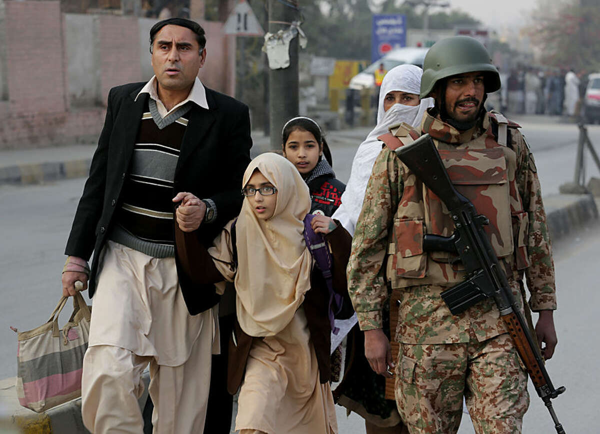 Pakistani parents escort their children outside a school attacked by THE Taliban in Peshawar, Pakistan, Tuesday, Dec. 16, 2014. Taliban gunmen stormed a military-run school in the northwestern Pakistani city of Peshawar on Tuesday, killing and wounding scores, officials said, in the highest-profile militant attack to hit the troubled region in months. (AP Photo/B.K. Bangash)