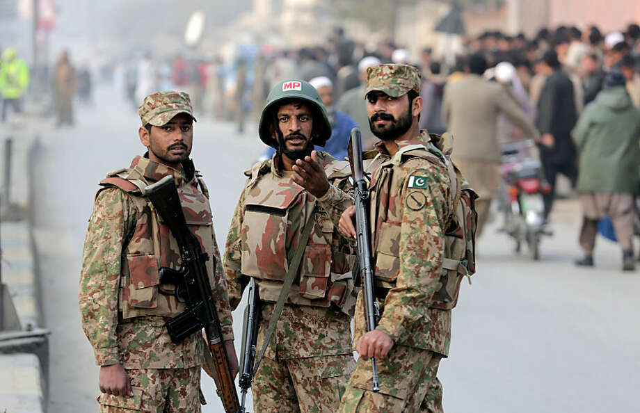 Pakistan army soldiers cordon off the area outside a school attacked by the Taliban in Peshawar, Pakistan, Tuesday, Dec. 16, 2014. Taliban gunmen stormed a military-run school in the northwestern Pakistani city of Peshawar on Tuesday, killing and wounding scores, officials said, in the highest-profile militant attack to hit the troubled region in months. (AP Photo/B.K. Bangash)