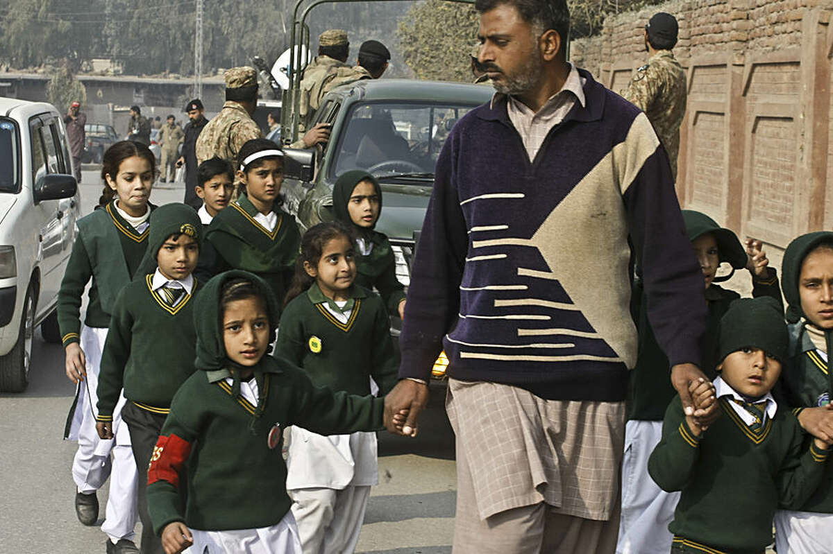 A plainclothes security officer escorts students evacuated from a school as Taliban fighters attack another school nearby in Peshawar, Pakistan, Tuesday, Dec. 16, 2014. Taliban gunmen stormed a military-run school in the northwestern Pakistani city, killing and wounding scores, officials said, in the worst attack to hit the country in over a year. (AP Photo/Mohammad Sajjad)