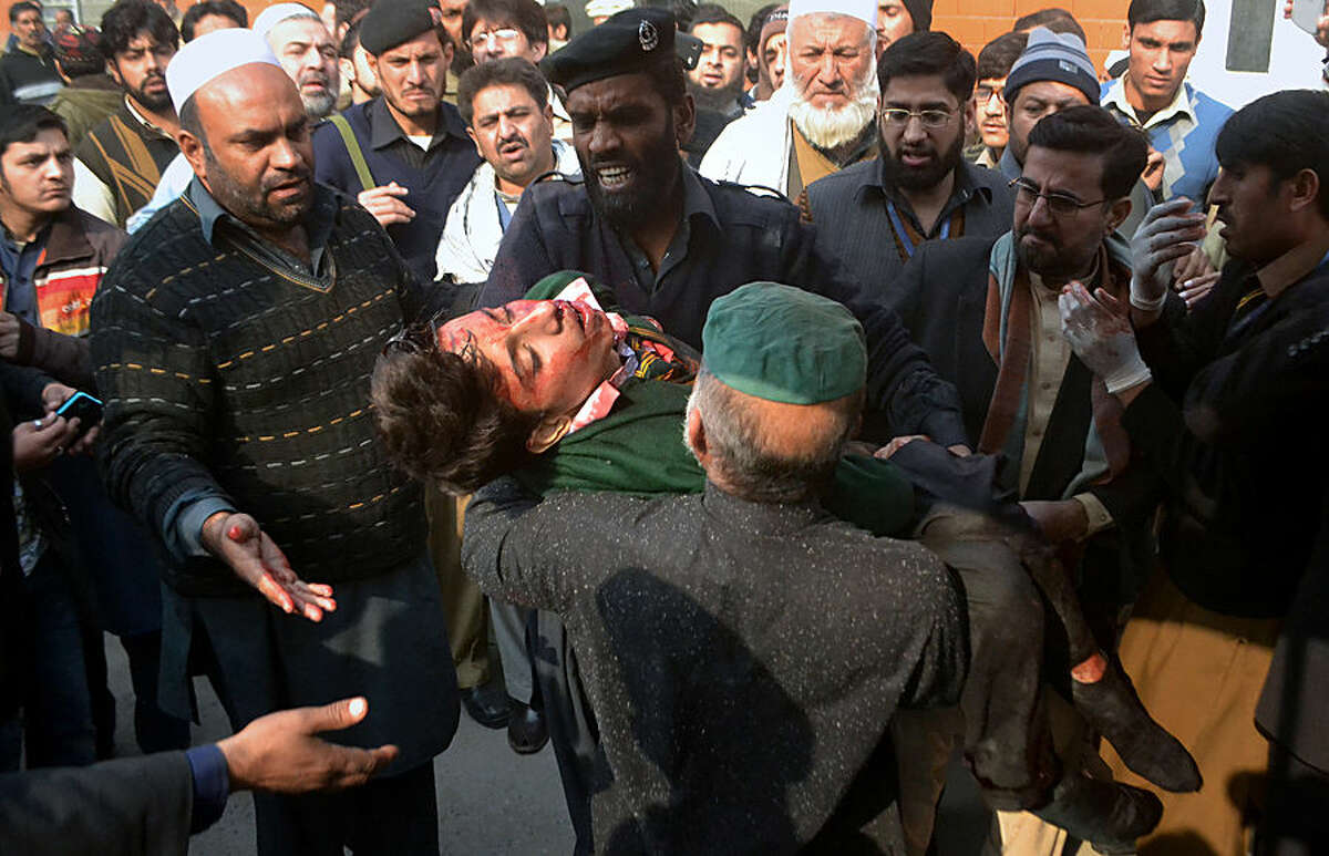 Hospital security guards carry a students injured in the shootout at a school under attacked by Taliban gunmen in Peshawar, Pakistan,Tuesday, Dec. 16, 2014. Taliban gunmen stormed a military school in the northwestern Pakistani city, killing and wounding dozens, officials said, in the latest militant violence to hit the already troubled region. (AP Photo/Mohammad Sajjad)(AP Photo/Mohammad Sajjad)