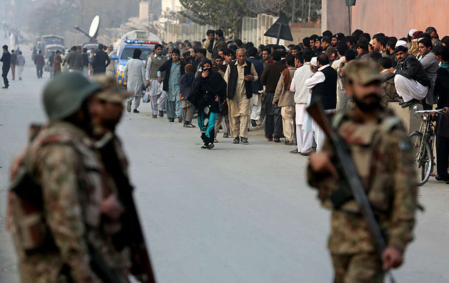 People wait for their kids outside a school attacked by the Taliban in Peshawar, Pakistan, Tuesday, Tuesday, Dec. 16, 2014. Taliban gunmen stormed a military-run school in the northwestern Pakistani city of Peshawar on Tuesday, killing and wounding scores, officials said, in the highest-profile militant attack to hit the troubled region in months. (AP Photo/B.K. Bangash)