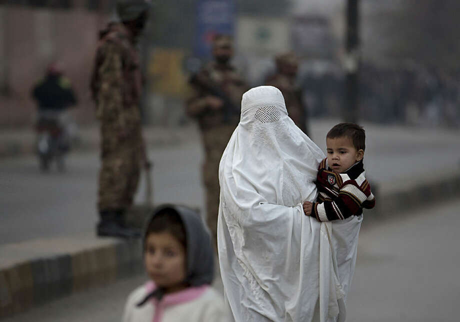 A Pakistani woman walks past a school attacked by the Taliban in Peshawar, Pakistan, Tuesday, Tuesday, Dec. 16, 2014. Taliban gunmen stormed a military-run school in the northwestern Pakistani city of Peshawar on Tuesday, killing and wounding scores, officials said, in the highest-profile militant attack to hit the troubled region in months. (AP Photo/B.K. Bangash)
