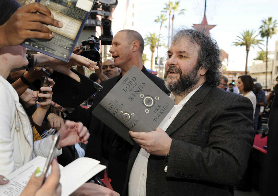 "FILE - In this Monday, Dec. 8, 2014 file photo, Peter Jackson, director, co-writer and producer of the film trilogies ""The Lord of the Rings and ""The Hobbit,"" takes a fan's copy of J.R.R. Tolkien's novel ""The Lord of the Rings"" to sign following a ceremony honoring Jackson with a star on the Hollywood Walk of Fame in Los Angeles. ""The Hobbit"" and ""The Lord of the Rings"" filmmaker Jackson, who crafted all six of the films in his native New Zealand, was similarly adamant during an interview in London to promote the final ""Hobbit"" that he was finished adapting J.R.R. Tolkien, though he would ""never say never"" to a Middle-earth homecoming. (Photo by Chris Pizzello/Invision/AP, File)"