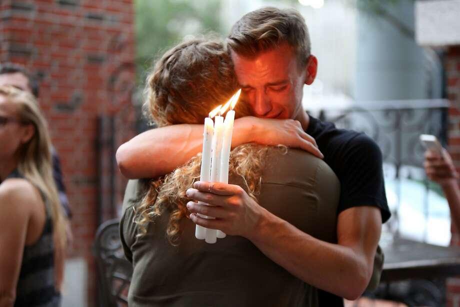 Brett Morian, from Daytona Beach, hugs an attendee during the candlelight vigil at Ember in Orlando, Fla., on Sunday. Photo: Joshua Lim, Associated Press