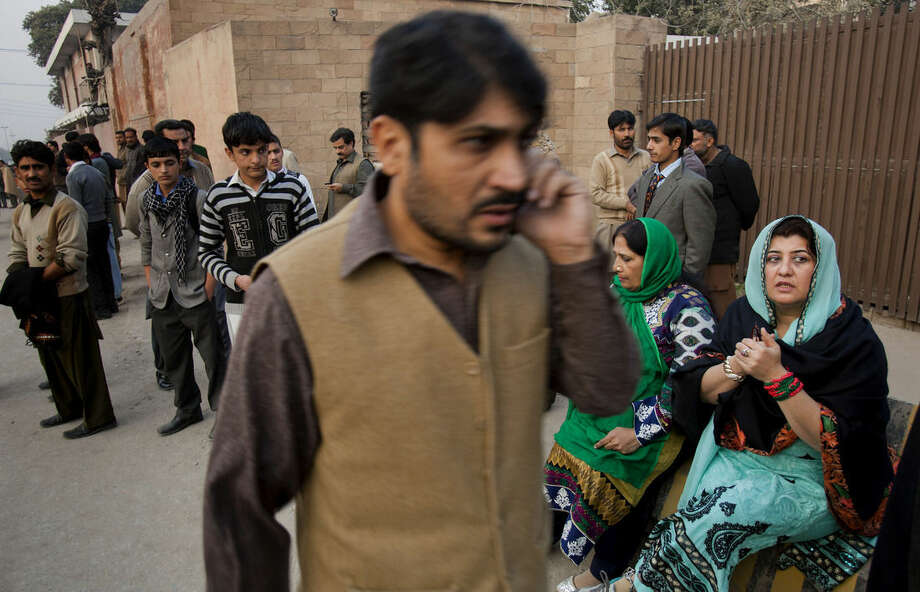 People wait for their children outside a school attacked by the Taliban in Peshawar, Pakistan, Tuesday, Dec. 16, 2014. Taliban gunmen stormed a military-run school in the northwestern Pakistani city of Peshawar on Tuesday, killing and wounding scores, officials said, in the highest-profile militant attack to hit the troubled region in months. (AP Photo/B.K. Bangash)