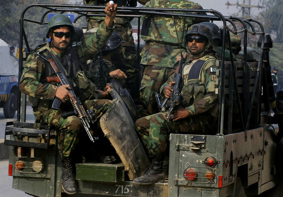 Pakistani army troops arrive to conduct an operation at a school under attack by Taliban gunmen in Peshawar, Pakistan, Tuesday, Dec. 16, 2014. Taliban gunmen stormed the military-run school in the northwestern Pakistani city, killing and wounding scores, officials said, in the highest-profile militant attack to hit the troubled region in months. (AP Photo/Mohammad Sajjad)