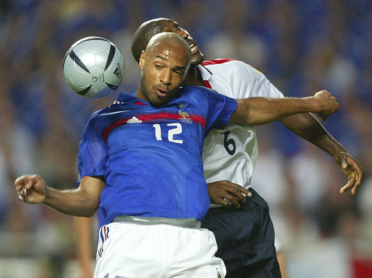 FILE - In this Sunday, June 13, 2004 file photo Thierry Henry, front, of France, is challenged by England's Sol Campbell during their the Euro 2004 Group B soccer match between England and France at Luz Stadium, in Lisbon, Portugal. Thierry Henry has announced his retirement following a 20-year career. The 37-year-old Henry, a member of the France teams that won the 1998 World Cup and 2000 European Championship, will take up a media role as a consultant for Sky Sports channel. (AP Photo/Thomas Kienzle, File)