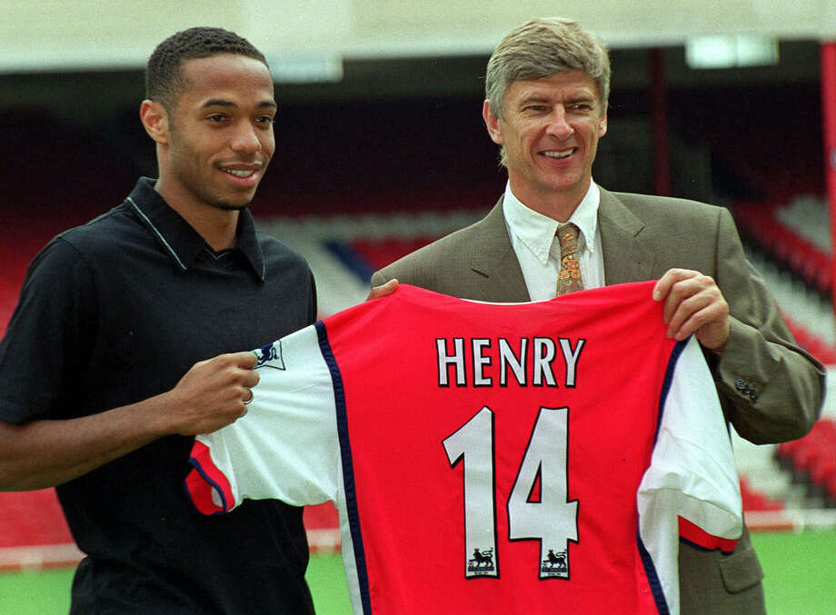FILE - In this Tuesday, August 3, 1999 file photo Arsenal's latest signing, Thierry Henry, left, with Manager Arsene Wenger, pictured at Highbury in north London. Thierry Henry has announced his retirement following a 20-year career. The 37-year-old Henry, a member of the France teams that won the 1998 World Cup and 2000 European Championship, will take up a media role as a consultant for Sky Sports channel. (AP Photo/Robin Nowacki, File)