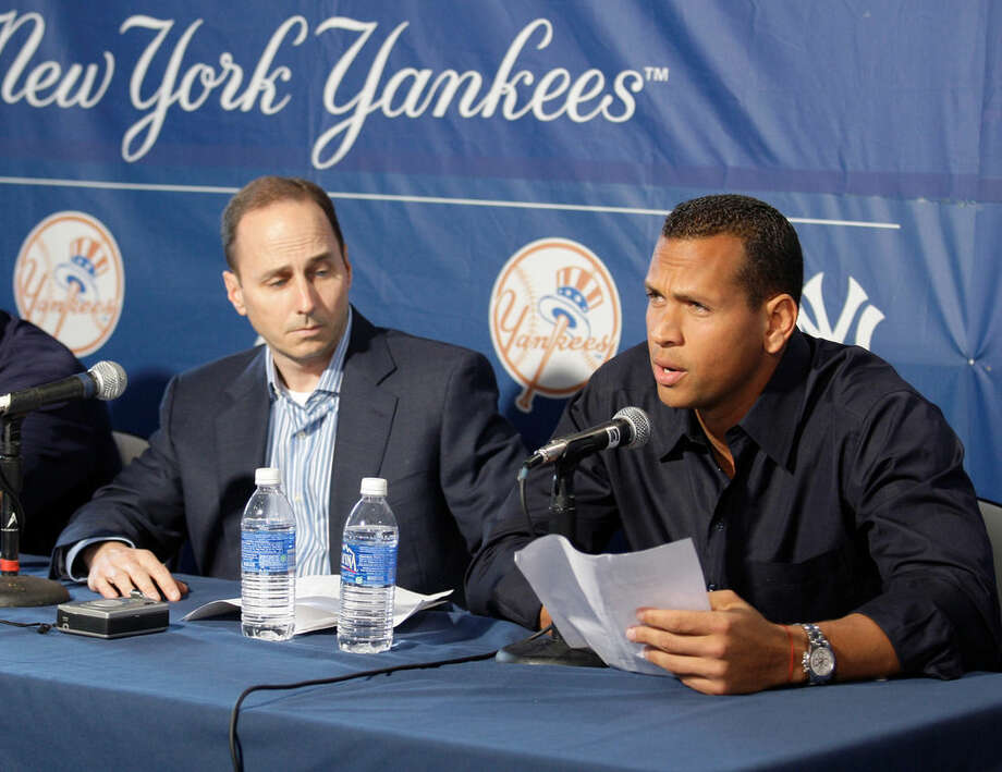 FILE - In this Feb. 17, 2009, file photo, New York Yankees' Alex Rodriguez reads a statement to the media alongside Yankees general manager Brian Cashman after arriving at George Steinbrenner Field in Tampa, Fla. Alex Rodriguez isn't yet at the weight the New York Yankees want him to be at when he reports to spring training in two months. Yankees general manager Brian Cashman said Matthew Krause, the team's strength and conditioning coordinator, visited A-Rod on Wednesday, Dec. 10, 2014, in Miami. (AP Photo/Gene J. Puskar, File)