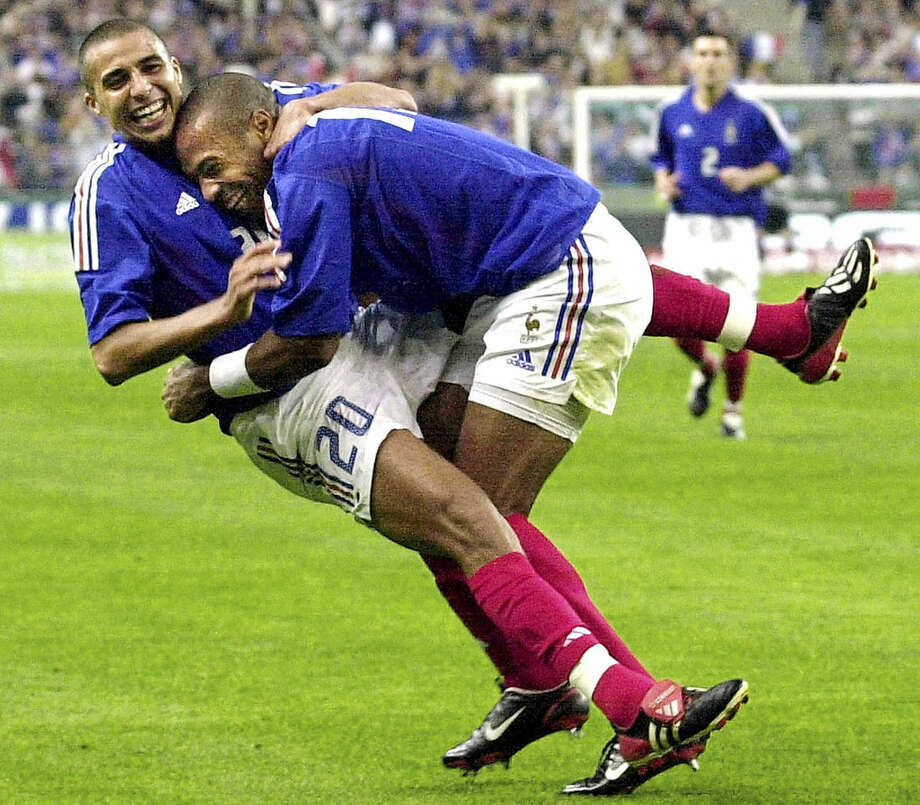 FILE - France's David Trezeguet, left, celebrates with teamate Thierry Henry after scoring against Israel during their Euro 2004 qualifying soccer match at the Stade de France in Saint Denis, north of Paris, in this Saturday Oct. 11, 2002, file photo. Thierry Henry has announced his retirement following a 20-year career. The 37-year-old Henry, a member of the France teams that won the 1998 World Cup and 2000 European Championship, will take up a media role as a consultant for Sky Sports channel. (AP Photo/Francois Mori,file)