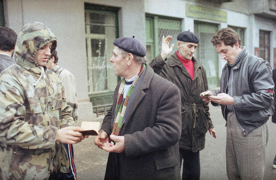 FILE - This is a Dec. 23, 1989 file photo of civilian guards checking the documents of passers-by on the streets of Timisoara, Romania, in search for the plain clothes pro-Ceausescu secret police members. More than 5,000 people were killed in Timisoara this week. Twenty-five years ago the people rose up against Romanian dictator Nicolae Ceausescu, executed him and set the country on a path to democracy. (AP Photo/Dusan Vranic, File)