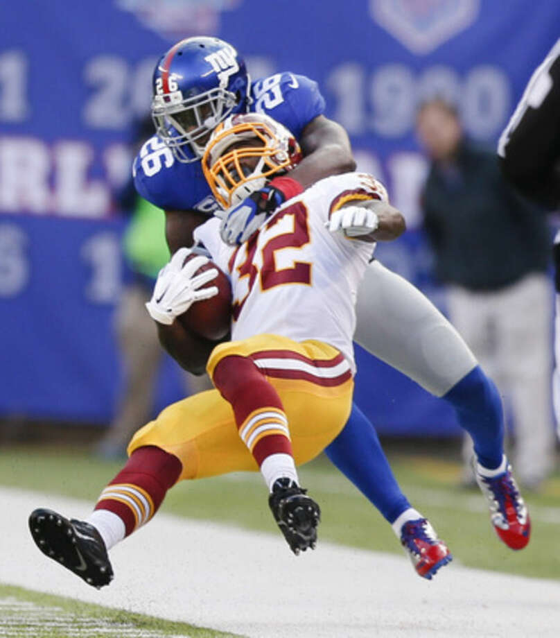 New York Giants strong safety Antrel Rolle (26) pulls Washington Redskins running back Silas Redd (32) out of bounds during the second quarter of an NFL football game, Sunday, Dec. 14, 2014, in East Rutherford, N.J. (AP Photo/Julio Cortez)