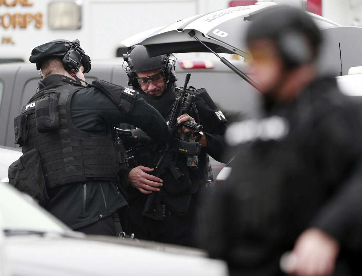 Police make preparations at a staging area for the search for suspect Bradley William Stone, Tuesday, Dec. 16, 2014, in Pennsburg, Pa. The manhunt for the Marine veteran suspected of killing his ex-wife and five of her relatives, amid a child custody dispute, has spread to two suburban Philadelphia counties. (AP Photo/Matt Rourke)