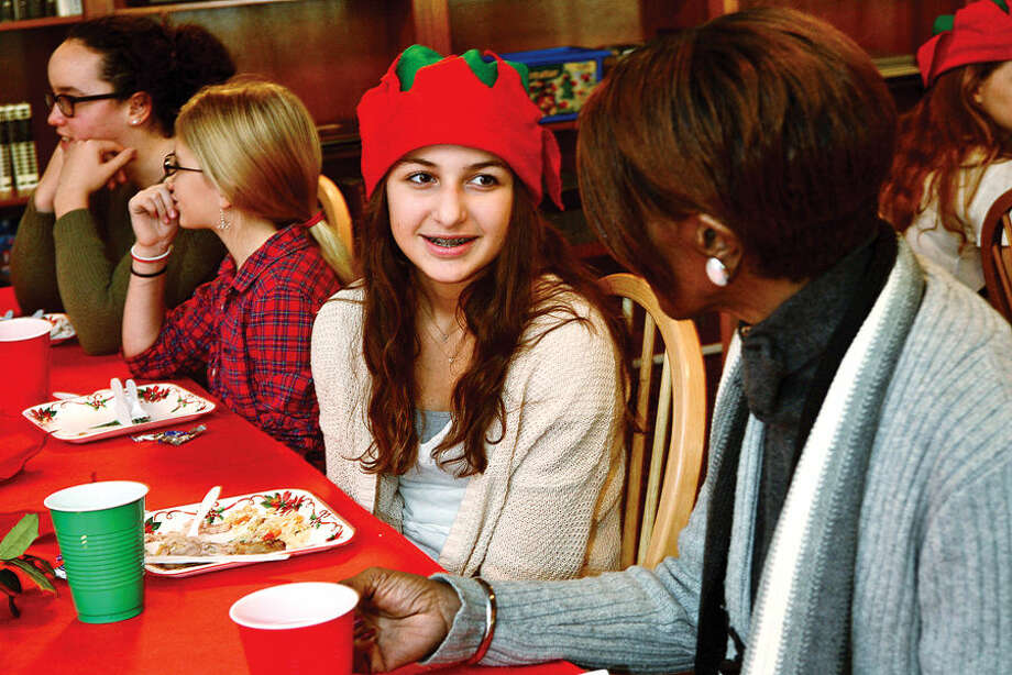 Hour photo / Erik Trautmann The Montessori School's middle school student Elizabeth Byer chats with Norwalk Shelter resident Sandra paige during the school's annual holiday Thursday lunch that they prepare and serve.