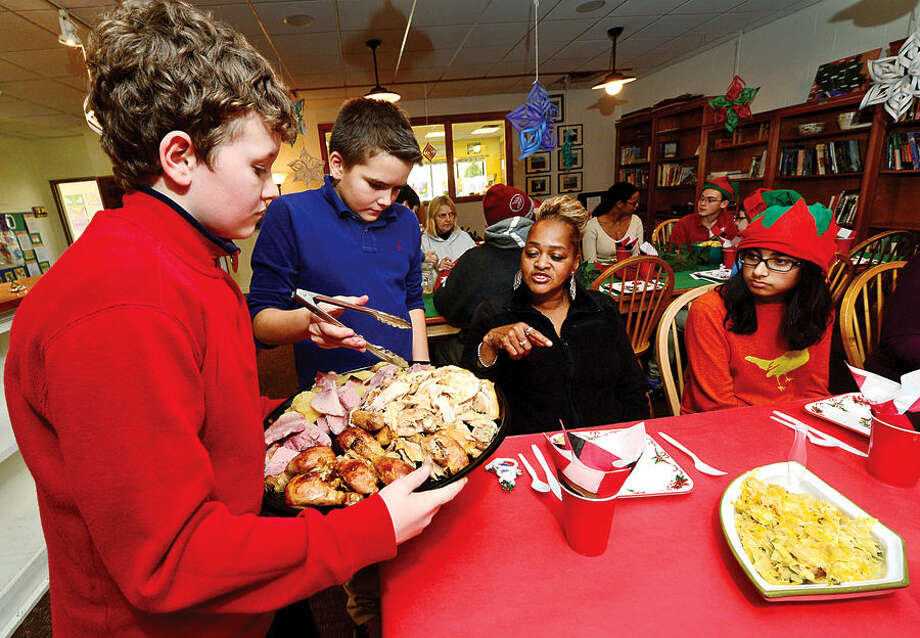 Hour photo / Erik Trautmann The Montessori School's middle school students Liam Breslin and Jack Czaja serve residents from the Norwalk Shelter including Linda Hallaway during the school's annual holiday lunch Thursday as student Saira Munshani, right, looks on.