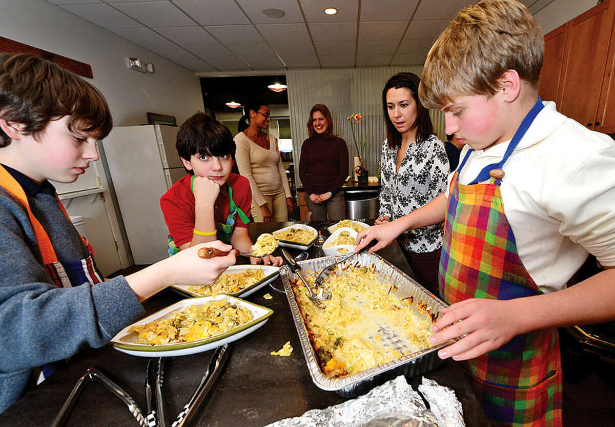 Hour photo / Erik Trautmann The Montessori School's middle school students Dylan Rosenbloom, BenO'Brien and Shane Cooper, prepare the school's annual holiday lunch Thursday to serve to residents of the Norwalk Shelter.