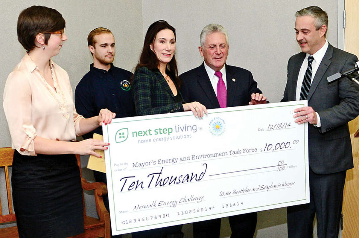 Hour photo / Erik Trautmann Erin O'Neill, Sr Program Manger at Next Step Living, Collin Babbage, Community Outreach Coordinator of New England Smart Energy and Stephanie Weiner, CEO of New England Smart Energy present a check for $10,000 to Mayor Harry Rilling and John Kydes, Coucilman and Chair of Mayor's Energy and Environmental Task Force for the newly formed Mayor's Student Engineering & Science program during a press conference at City Hall Thursday morning.