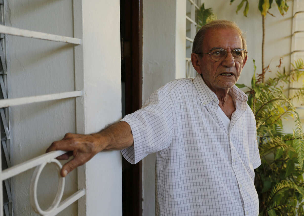 Rolando Sarraff stands at the entrance of his home in Havana, Cuba, Thursday, Dec. 18, 2014. A former intelligence official in the United States Thursday publically identified Rolando's son as the unnamed spy traded for three Cuban intelligence agents jailed in the United States, one who U.S. President Barrack Obama hailed as Washington's most valuable assets. But neither Cuban nor American officials have confirmed that Sarraff was spirited off the island and his parents have not heard from their son since he supposedly was freed. (AP Photo/Desmond Boylan)
