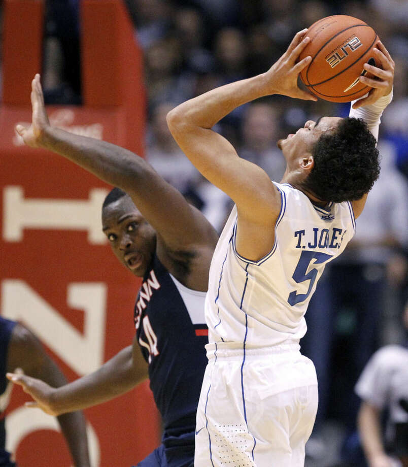 Connecticut forward Rakim Lubin, left, defends against Duke guard Tyus Jones during the first half of an NCAA college basketball game, Thursday, Dec. 18, 2014, in East Rutherford, N.J. (AP Photo/Julio Cortez)