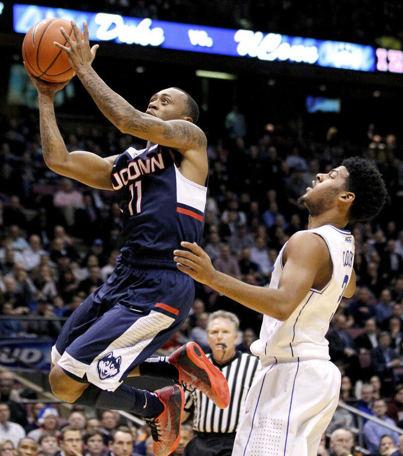 Connecticut guard Ryan Boatright (11) goes up to shoot against Duke guard Grayson Allen (3) during the first half of an NCAA college basketball game, Thursday, Dec. 18, 2014, in East Rutherford, N.J. (AP Photo/Julio Cortez)