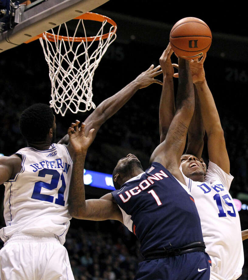 Connecticut forward Phillip Nolan (1) goes up for a rebound against Duke forward Amile Jefferson (21) and center Jahlil Okafor (15) during the first half of an NCAA college basketball game, Thursday, Dec. 18, 2014, in East Rutherford, N.J. (AP Photo/Julio Cortez)