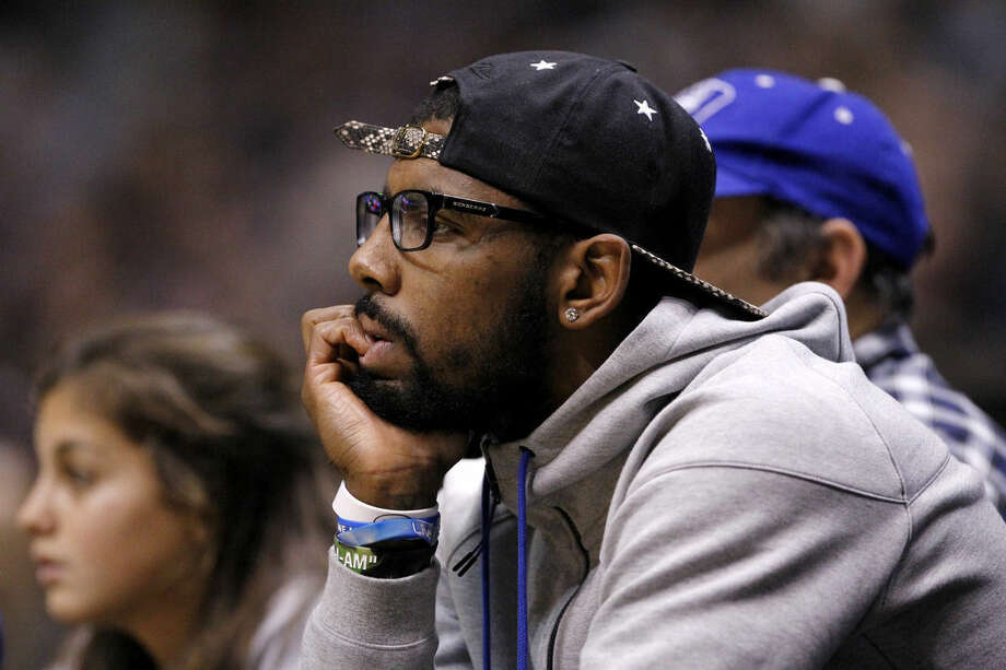 Former Duke basketball player Kyrie Irving watches the first half of an NCAA college basketball game between the Duke and the Connecticut, Thursday, Dec. 18, 2014, in East Rutherford, N.J. (AP Photo/Julio Cortez)