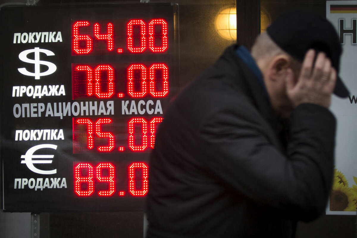FILE - In this Tuesday, Dec. 16, 2014, file photo, a man walks by a sign advertising currencies of an exchange office in Moscow. Russia has been badly affected by the slide in oil prices in 2014, and the ruble has plunged despite big increases in interest rates as much of Russia's economy is based on energy. (AP Photo/Alexander Zemlianichenko, File )