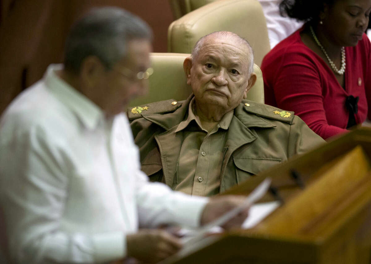 Commander of the Revolution Guillermo Garcia Frias listens to Cuba's President Raul Castro during the closing of the legislative session at the National Assembly in Havana, Cuba, Saturday, Dec. 20, 2014. While praising the historic agreement between Cuba and the U.S. to restore relations, Castro made it clear that the agreement only goes so far, reminding the audience of his call for the U.S. Congress to end the trade embargo. (AP Photo/Ramon Espinosa)