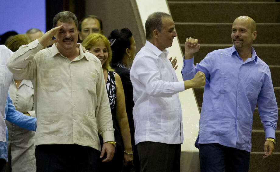 "Ramon Labanino, member of ""The Cuban Five,"" salutes members of the National Assembly as he stands with Antonio Guerrero, center, and Gerardo Hernandez at the end of the twice-annual legislative session in Havana, Cuba, Saturday, Dec. 20, 2014. The three men flew back to their homeland on Wednesday in a quiet exchange of imprisoned spies, part of a historic agreement to restore relations between Cuba and the U.S. Two members of The Cuban Five, Fernando and Rene Gonzalez, had been previously released by the U.S. (AP Photo/Ramon Espinosa)"