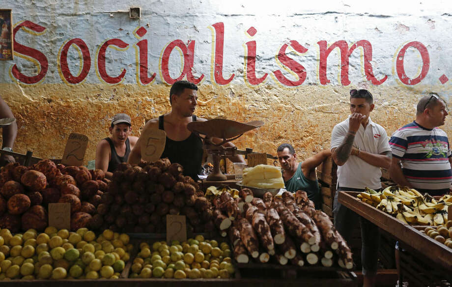 Workers stand behind their food stalls at a state-run market in Havana, Cuba, Saturday, Dec. 20, 2014. After the surprise announcement on Wednesday of the restoration of diplomatic ties between Cuba and the U.S., many Cubans expressed hope that it will mean greater access to jobs and the comforts taken for granted elsewhere, and lift their struggling economy. However others feared a cultural onslaught, or that crime and drugs, both rare in Cuba, will become common along with visitors from the U.S. (AP Photo/Desmond Boylan)