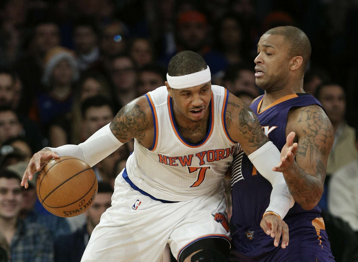 Phoenix Suns' P.J. Tucker defends New York Knicks' Carmelo Anthony, left, during the first half of an NBA basketball game Saturday, Dec. 20, 2014, in New York. (AP Photo/Frank Franklin II)