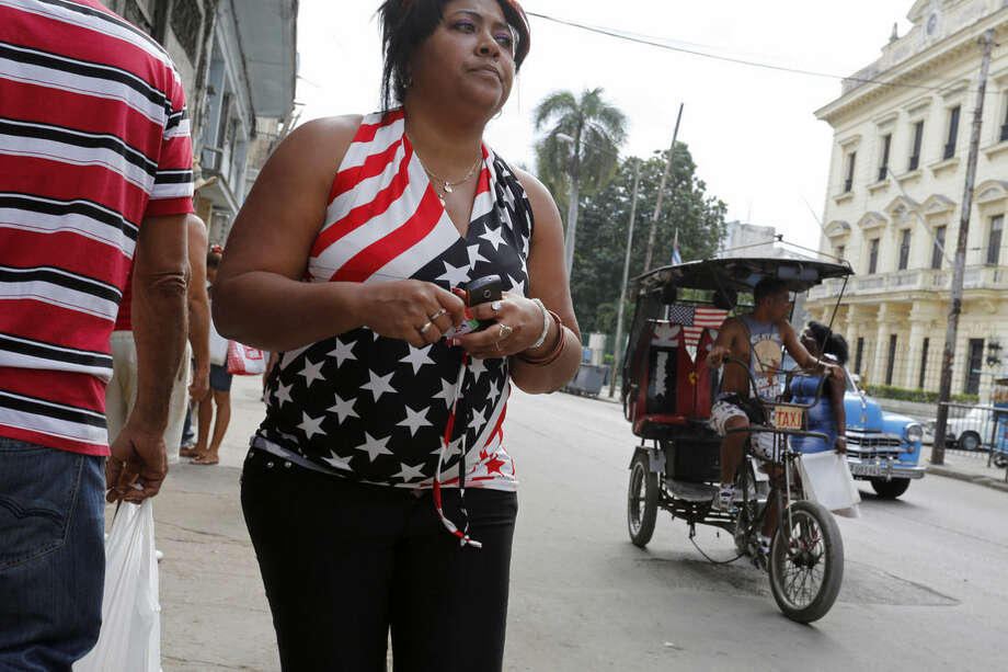 A woman wears a shirt decorated with the U.S. flag, as a tricycle taxi, also sporting a U.S. flag, pedals by in Havana, Cuba, Saturday, Dec. 20, 2014. After the surprise announcement on Wednesday of the restoration of diplomatic ties between Cuba and the U.S., many Cubans expressed hope that it will mean greater access to jobs and the comforts taken for granted elsewhere, and lift their struggling economy. However others feared a cultural onslaught, or that crime and drugs, both rare in Cuba, will become common along with visitors from the U.S. (AP Photo/Desmond Boylan)